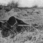 Sniper observing with a Scout Regiment Telescope among the sand dues on the German island of Sylt at a British Army sniping school.