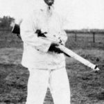 British sniper wearing a white snow suit and carrying his sniper rifle.