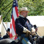 # 729 - Officer on horseback reviewing Union troops in camp before battle.