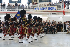 (360) Vancouver Police Pipe Band under the Welcome Home banner.