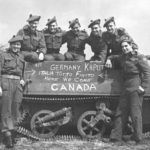 "Group of ""D"" Company, Seaforth of C. personnel posing with Universal Carrier, 7 May 1945 in Holland. Another photo taken a few minutes before had VANCOUVER chalked on the side. This was rubbed out and CANADA chalked in to accommodate Seaforths who were not from Vancouver."