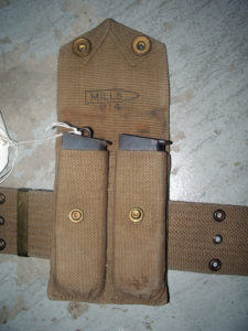 The MILLS 1914 magazine pouch with two magazines for Colt 1911 Commercial pistol, one of 5,000 purchased by Canada in 1914, serial number C13085. Shows the MILLS (inside a cartridge) . On the magazine on the right, the staple has broken off.