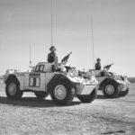 Two white Ferretr Scout Cars driving by with commander standing at attention in each one. United Nations flag in the foreground.