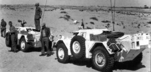 Two Ferret Scout Cars stopped in the desert. Men standing around.