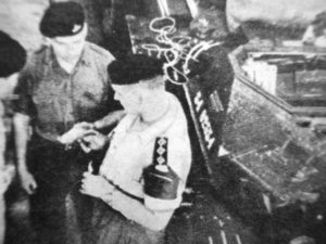 Men standing beside a Ferretr Scout Car.