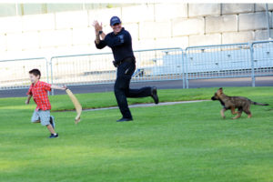 Police dog handler with puppy police dog and young boy with a drag for the puppy to grab. with his teeth. (D7100a 014)