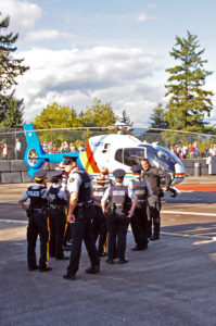 """""""Hey Sergeant! The Pilot says I am too big to go up in the helicopter!"""" RCMP members (regular and Auxilliary) talking with the helicopter pilot."""