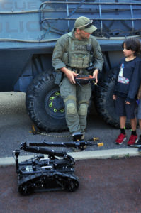 """""""Hey kid, can you show me how to work this thing?"""" Emergency Response Team member with remote controlled robot and a visitor."""