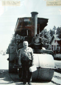 Man standing in front of a steam roller that he operated.