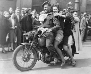 Captain W. L. Roberts on motorcycle Amsterdam May 1945 with three women on the back. This photo was used to make a Dutch postage stamp.