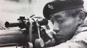 Gurkha sniper aiming his L42A1 sniper rifle.