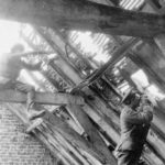Sniper in rafter of a barn and observer lower down.