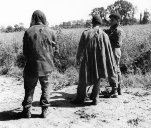 Three soldiers talking about a mission. They are standing and facing away from the camera.