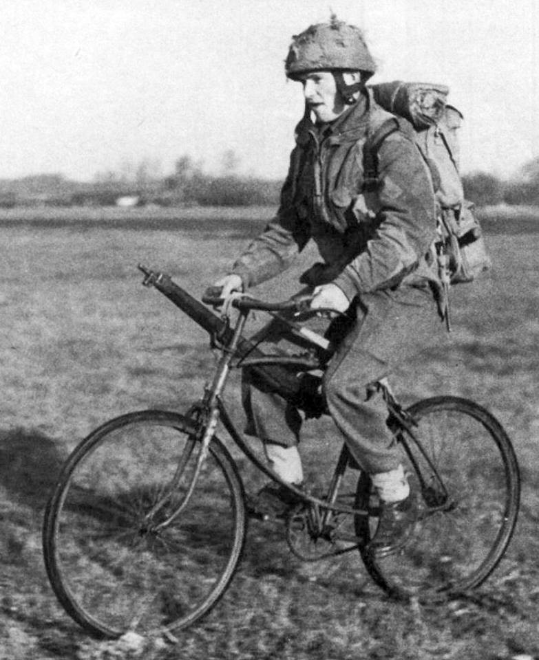 British airborne soldier riding a BSA airborne bicycle. There are no clips for the rfle, he is just using the sling looped over the handlebar and seat post.