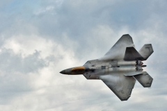 U.S.A.F. F-22 Raptor stealth fighter.  Moist air condensing off top of wings during a fast low pass. 2015